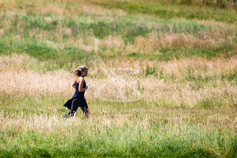 A woman runs through the grass on Parliament Hill on another hot day in London. London, July 03 2018.