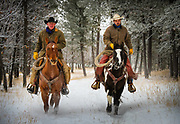 Two cowboys Nick and Michael) riding their horses down a snowy road in a wooded area near New Haven ranch in Wyoming