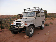 classic FJ40 Toyota Land Cruiser parked on a dirt driveway in Moab, Utah