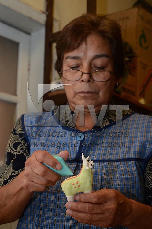 Toluca, México.- Trinidad Flores Serrano, con 40 años de trayectoria es la tercer generación en su familia en realizar de manera artesanal diversas figuras de alfeñique en donde la vende año con año en la tradicional feria del alfeñique de la capital mexiquense. Agencia MVT / Arturo Hernández.