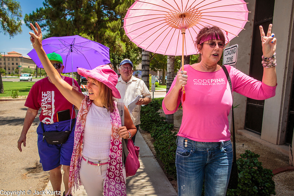 """31 JULY 2012 - PHOENIX, AZ:  MEDEA BENJAMIN, left, and other members of Code Pink march around the Arizona State Capitol Tuesday. Medea is a political activist, best known for co-founding Code Pink and, along with her husband, activist and author Kevin Danaher, the fair trade advocacy group Global Exchange. She was also a Green Party candidate in 2000 for the United States Senate. She appeared in Phoenix to promote her new book, """"Drone Warfare: Killing by Remote Control."""" She, and other members of Code Pink, presented a letter to Arizona Gov. Jan Brewer protesting Brewer's request to use the state's airspace to train drone pilots.  PHOTO BY JACK KURTZ"""