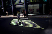 A woman pedestrian runs through green reflected light shining from a City of London office building.