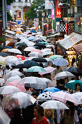 Rainy day with many umbrellas in Takeshita Street in trendy Harajuku Tokyo Japan