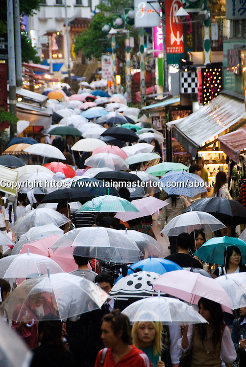 Rainy day with many umbrellas in Takeshita Street in trendy Harajuku Tokyo Japan