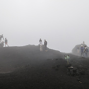 A group of tourists pose for photos at a cloudy and misty summit of Pacaya Volcano. Pacaya is an active volcano that forms part of the Central America Volcanic Arc. It forms a popular tourist destination easily accessible from Antigua and Guatemala City. Situated within the Pacaya National Park, it rises to 2,552 metres (8,373 ft). Its last major eruption, which caused considerable damange to nearby villages and reshaped the summit, was in May 2010. That eruption and scattered volcanic ash over much of the nearby area, prompting school closings and emergency evacuations and cleared much of the vegetation near the top of the mountain.