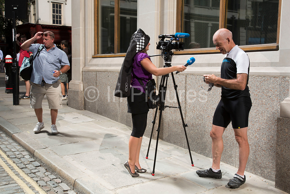 """London, UK. Wednesday 4th September 2013. Man being interviewed by tv news while checking his watch for the temperature. Urgent action in planned to """"cover up"""" the Walkie Talkie skyscraper in the City after sunlight reflected from the building melted a car on the streets below. Temperatures have been measured in excess of 50 degrees C, and as much as 70 degrees at it's peak. The 525ft building has been renamed the """"Walkie Scorchie"""" after its distinctive concave surfaces reflected a dazzling beam of light which has caused extensive damage to nearby buildings."""