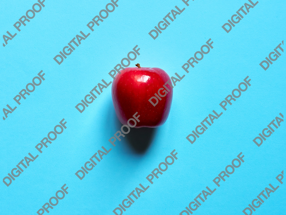 Red apple viewed from above over a blue background isolated in studio
