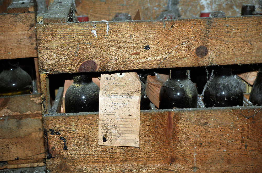 An old wooden crate of bottles of Banyuls wine sealed for inspection by the INAO according to the label, Cellier des Dominicains in Collioure, Languedoc-Roussillon, France