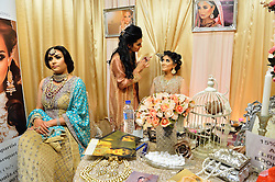 © Licensed to London News Pictures. 27/03/2016. A couple of models have their make-up done on a beauty stand at the Asian Bride Live Wedding Show featuring fashion, beauty and services for brides to be. London, UK. Photo credit: Ray Tang/LNP