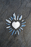 Selenite Heart with Kyanite. Still Life Photography. Selenite is one of the most important tools to have in your energy tool kit because it doesn't need to be recharged. ... Its ability to not dull as it absorbs and dissipates negative energy is why it is so often used to cleanse and recharge other crystals. The powerful vibration of Selenite can clear, open, and activate the Crown and Higher Chakras and is excellent for all types of spiritual work or meditation. ... Selenite can evoke protection from the angelic realm and also dispels negative energy. Also, it removes energy blocks from physical and etheric bodies. Selenite Crystal is a stone shaped from the mineral gypsum, which comes in numerous varieties. Selenite is named for Selene, goddess of the moon. It is identified with higher awareness and is used to help with reflection and astral projection. <br /> <br /> Kyanite is an aluminium silicate that is a member of the silicate group of minerals.This stone encourages you to speak your truth by cutting though fears and blockages. Kyanite opens the throat chakra and encourages self expression and communication.
