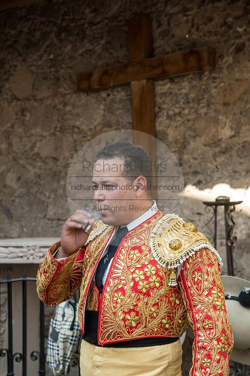 A Mexican Matador smokes a cigarette before entering the bull ring for the bullfights at the Plaza de Toros in San Miguel de Allende, Mexico.