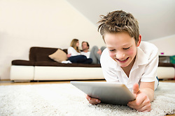Happy boy in living room using digital tablet with parents in background