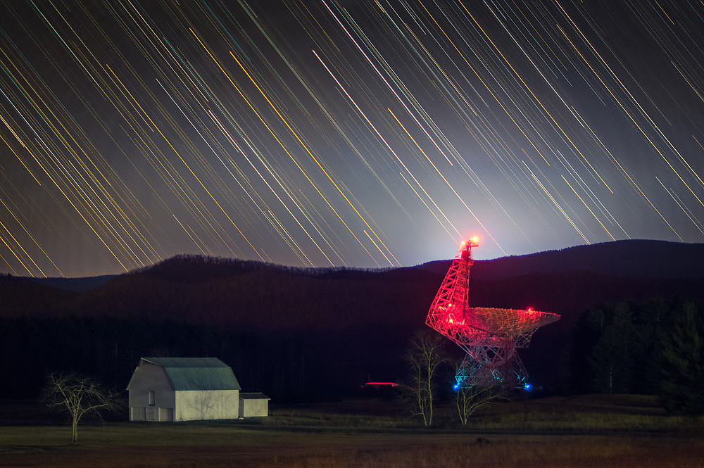 The National Radio Observatory in Green Bank, West Virginia is home to the world's largest steerable radio telescope, sensitive enough to provide a look into the origins of the Universe, here it is captured at a distance over time with the passage of time marked by the trails of stars in the sky above.