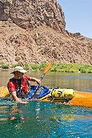 Kayaker rolls his wooden boat on The Colorado River, The Black Canyon, Nevada.