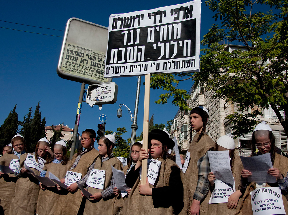 Thousands of ultra orthodox Jewish men and children rally in the religious neighborhood of Mea Shearim in Jerusalem, carrying signs in Hebrew that call to save Jerusalem from destruction, on July 8, 2009, during a demonstration against the opening of a car park during the Sabbath. A series of protests centre on the decision by the municipality to require a car park outside the walls of the Old City to open on Friday and Saturday, when religious Jews observe a day of rest.