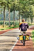 Nederland, Aalten, 28-8-2019Een manlijke postbezorger rijdt, fietst over een weg in het buitengebied .Foto: Flip Franssen