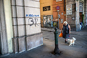 An elderly woman and her pet dog cross the street in Genoa, Italy.