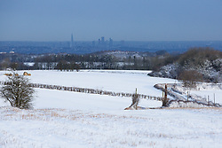 Licensed to London News Pictures. 13/01/2017. Warlingham, UK.  London and the Shard are seen from a snow covered Botley Hill in Surrey today (13/01/2017), after snow swept through parts of the UK yesterday. Further snow is predicted later today with many parts of the UK disrupted due to severe weather. Photo credit: Matt Cetti-Roberts/LNP