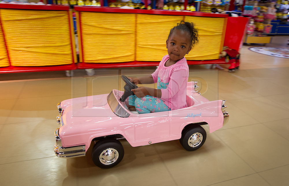 © Licensed to London News Pictures. 27/06/2013. London, UK. Jayla, 3, pedals a Hollywood Pedal Car (Hamleys price GB£250) at the Christmas in June press event at Hamleys toy shop in London today (27/06/2013).  Held in retailers world famous Regents Street store, the event showcases the predicted top toys for Christmas 2013. Photo credit: Matt Cetti-Roberts/LNP