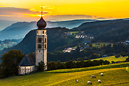 Tyrolean church with a clocktower in the middle of a meadow abowe a town