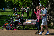 Happy to be eating ice cream  but also breaking the no sitting rules, as dog walkers chat, spaced out, in the background - it is the clear dilema of easing lockdown. The cafe near the closed bandstand is now open, for drinks and ice cream, with a one way system and social distancing. Clapham Common is reasonably busy as the sun is out and it is warmer. The 'lockdown' continues for the Coronavirus (Covid 19) outbreak in London.