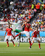Joe Ledley of Wales jumps for a header with Kyle Lafferty of Northern Ireland. UEFA Euro 2016, last 16 , Wales v Northern Ireland at the Parc des Princes in Paris, France on Saturday 25th June 2016, pic by  Andrew Orchard, Andrew Orchard sports photography.