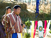 A Bhutanese man wearing a traditional 'gho' at an archery tournament, Thimphu, Western Bhutan. 'Datse' (archery) is Bhutan's national sport and is played wherever there is enough space and remains the favourite sport for men of all ages. There are archery tournaments held throughout the country. The targets are placed 140m apart. If the contestant hits his target, his team mates will perform a slow dance and sing his praises, while he slips a coloured scarf into his belt.