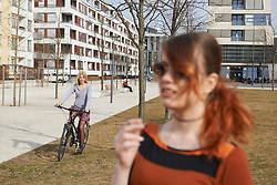 Teenage girl riding bicycle and young woman with cigarette in foreground, Munich, Bavaria, Germany