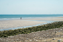 A small lone figure walking along Bridlington North Beach <br />