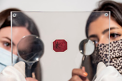 © Licensed to London News Pictures. 28/04/2021. LONDON, UK.  Staff members present the legendary 1856 British Guiana One-Cent Magenta stamp (Est. $10–15m at Sotheby's New Bond Street.  The sole survivor of its kind, it was created as a contingency when a shortage of stamps usually imported from England threatened to disrupt the postal service throughout British Guiana. Each of the four times it has sold at auction, it has established a new record price for a single stamp and will be part of the auction collection of high-end shoe designer Stuart Weitzman at Sotheby's New York on 8 June.  Photo credit: Stephen Chung/LNP