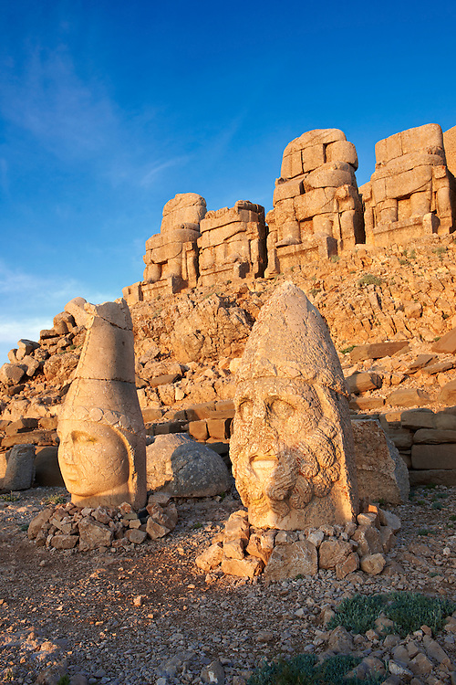 Image of the statues of around the tomb of Commagene King Antochus 1 on the top of Mount Nemrut, Turkey. Stock photos & Photo art prints. In 62 BC, King Antiochus I Theos of Commagene built on the mountain top a tomb-sanctuary flanked by huge statues (8–9 m/26–30 ft high) of himself, two lions, two eagles and various Greek, Armenian, and Iranian gods. The photos show the broken statues on the  2,134m (7,001ft)  mountain. 3