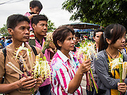 "22 JULY 2013 - PHRA PHUTTHABAT, THAILAND: People wait to present flowers to monks during the Tak Bat Dok Mai at Wat Phra Phutthabat in Saraburi province of Thailand, Monday, July 22. Wat Phra Phutthabat is famous for the way it marks the beginning of Vassa, the three-month annual retreat observed by Theravada monks and nuns. The temple is highly revered in Thailand because it houses a footstep of the Buddha. On the first day of Vassa (or Buddhist Lent) people come to the temple to ""make merit"" and present the monks there with dancing lady ginger flowers, which only bloom in the weeks leading up Vassa. They also present monks with candles and wash their feet. During Vassa, monks and nuns remain inside monasteries and temple grounds, devoting their time to intensive meditation and study. Laypeople support the monastic sangha by bringing food, candles and other offerings to temples. Laypeople also often observe Vassa by giving up something, such as smoking or eating meat. For this reason, westerners sometimes call Vassa the ""Buddhist Lent.""     PHOTO BY JACK KURTZ"