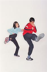 Young boy and girl kicking,