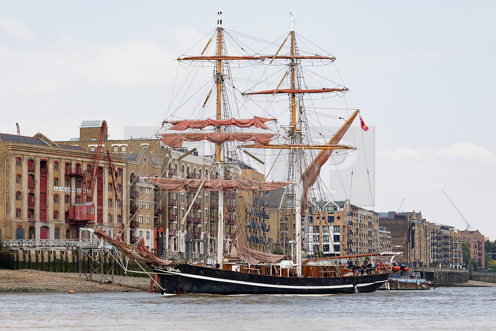"""© Licensed to London News Pictures. 23/05/2018. London, UK. The 107 year old tall ship, """"Eye of the Wind"""" sails on the River Thames in front of historic wharves in Wapping during a London visit to join celebrations to mark forty years since the start of Operation Drake - a two year round the world expedition, of which Eye Of The Wind was the flagship. One of the last traditional sailing ships left, Eye of the Wind was originally built in Germany in 1911 as a Schooner but was given a new lease of life in 1973 when she was bought by Anthony """"Tiger"""" Timbs, an Englishman from greater London. A group of enthusiastic ship lovers began to rig the vessel as a brigantine and her full restoration at a shipard in Faversham, Kent took nearly four years to complete. Photo credit: Vickie Flores/LNP"""