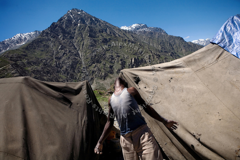 A labourer has just woken up and is stretching outside his tent on the Leh-Manali Highway.