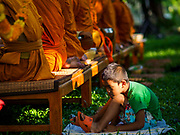 "17 MARCH 2018 - BANGKOK, THAILAND:  A boy sits on the ground behind a row of monks and listens to them during a ""sticky rice merit making"" in Lumpini Park in Bangkok. Sticky rice merit making is a merit making in the Isan / Lao style, when people present small amounts of cooked sticky rice (also known as glutinous rice) to Buddhist monks. Isan is the northeast region of Thailand.     PHOTO BY JACK KURTZ"