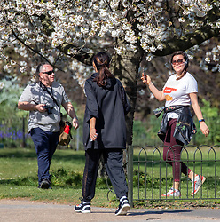 © Licensed to London News Pictures. 05/04/2020. London, UK. A young women enjoys a walk in the warm weather as others walk by. Members of the public come out to exercise In Hyde Park as temperatures reach over 21c this weekend. Hyde Park was busy with walkers, runners and cyclists as the Government urged the public not to leave home during the fine weather as the Coronavirus crisis continues. Photo credit: Alex Lentati/LNP