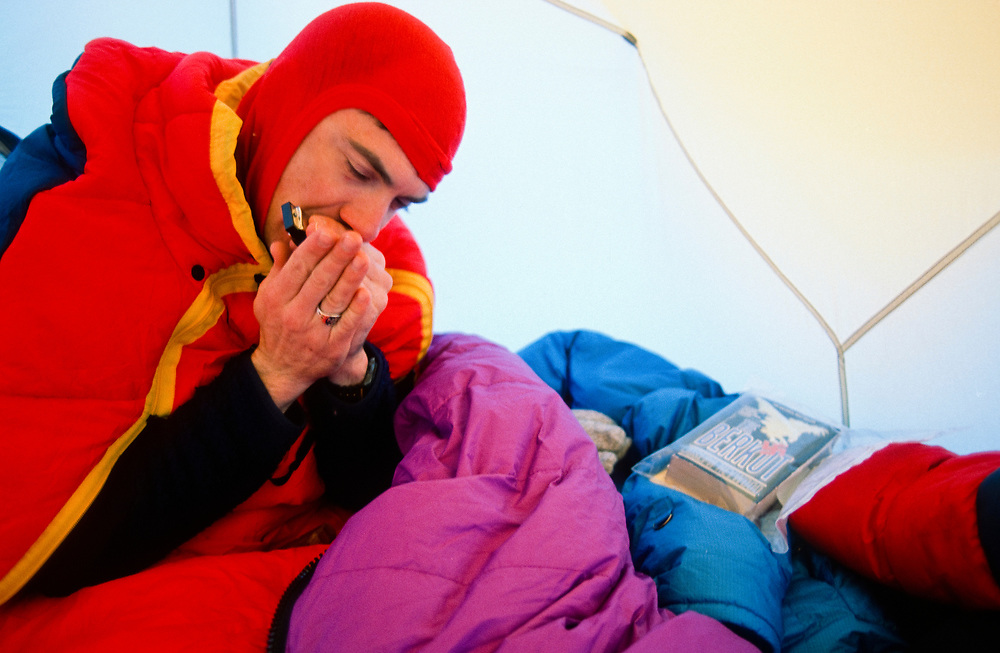 Alaska. Climber Rick Ford plays harmonica while tent-bound at 11,000' on Denali. MR