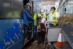 Edinburgh, Scotland, UK. 15 Feb 2021. From today Scottish Government requires all passengers from overseas arriving at Scottish airports to go into a mandatory quarantine in a hotel. Pic; First family who transited to Scotland via Dublin to go into quarantine arrives at Edinburgh airport and are escorted onto a bus that will take them to a guarded hotel for quarantine. Iain Masterton/Alamy Live news