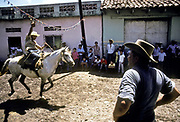 "Local villagers take part in a "" Corrida de Cintas"" where a horse rider gallops down the village street  and must incert a pencil through a small ring held high on a wire  that straddles the street. The winner receives a kiss on the cheek by a local beauty ""queen"", Nueva Esparta town, El Salvador."