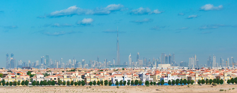 Skyline panorama of Dubai with modern luxury villas at The Villa residential housing development in foreground in United Arab Emirates