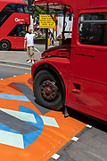 As two London buses pass in different directions, an anxious-looking pedestrian waits to cross the multi-coloured markings of a crossing at Piccadilly Circus, on 16th July 2021, in London, England.