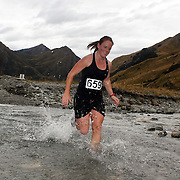 Runner Maria Turner crosses  Moke Creek on the Ben Lomond High Country Station during the Pure South Shotover Moonlight Mountain Marathon and trail runs. Moke Lake, Queenstown, New Zealand. 4th February 2012. Photo Tim Clayton