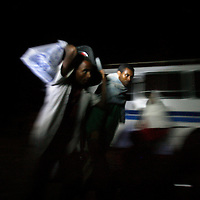 Ethiopian men carry their bags to a bus before dawn as a group of 46 Falash Mura people leave the compound in Gondar to a 24 hours journey to Addis Ababa in order to immigrate to Israel, May 11, 2008.