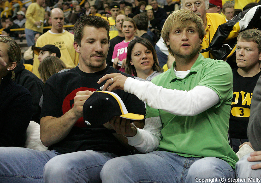 15 FEBRUARY 2007: Nate Kaeding (K - San Diego Chargers) hands a hat to Dallas Clark (TE - Indianapolis Colts) to sign during in Iowa's 66-58 win over Northwestern at Carver-Hawkeye Arena in Iowa City, Iowa on February 15, 2007.