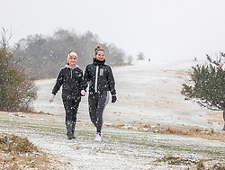 © Licensed to London News Pictures. 08/02/2021. Surrey, UK. Walkers Kelly Franky and daughter Brill enjoy the blizzard like snow conditions on top of Box Hill in Surrey this morning as Storm Darcy hits the South East with more snow and freezing temperatures today. The Met Office have issue numerous weather warnings for heavy snow and ice with disruption to travel, power cuts and possible stranded vehicles as the bad weather continues.  Photo credit: Alex Lentati/LNP