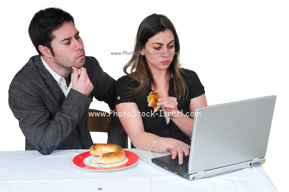 Male and female office workers take a luch break while still at their workstation. Not paying attention to food consuption is a major health and life quality degrader