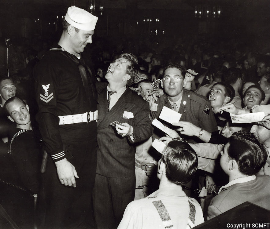 1943 Mickey Rooney looks up at Mickey Simpson at the Hollywood Canteen