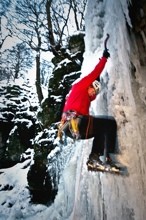 Ed Chard Ice Climbing at The Waterfall Swallet near Eyam, Derbyshire, Peak District National Park, England, UK.