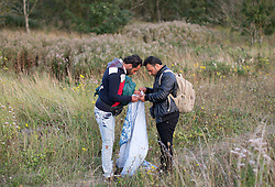 © Licensed to London News Pictures. 29/08/2015. Calais, France. A couple of refugees from Syria fold a blanket on their way way to the perimeter fences to attempt their way out to UK through the Channel Tunnel in Frethun, near Calais. Photo credit : Isabel Infantes/LNP